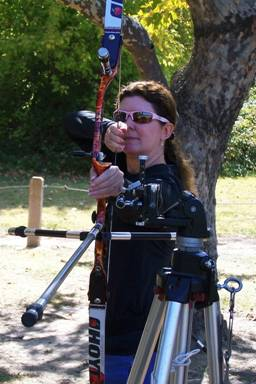 Photo of Janice at full draw.  She is lining up her shot by touching the back of her hand to the sight mounted on the tripod.